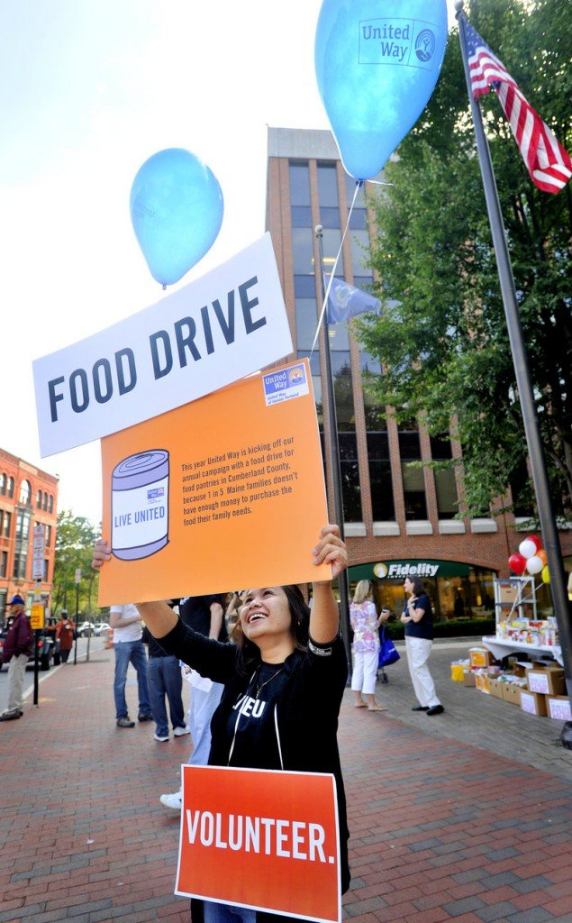 Madge Gardo, a United Way volunteer from Gorham Savings Bank, urges passers-by to donate as the Greater Portland United Way kicked off its annual campaign with a food drive at Canal Plaza in Portland on Thursday. Cumberland County was hit this year by a loss of $143,000 in federal funds for the Emergency Food and Shelter Program.