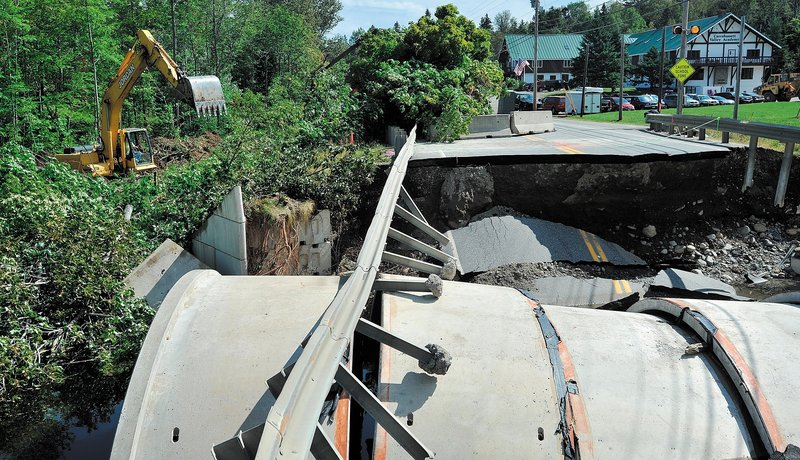 Reed & Reed construction workers begin the process of building a temporary bridge over Brackett Brook on Route 27 in Carrabassett Valley on Thursday.