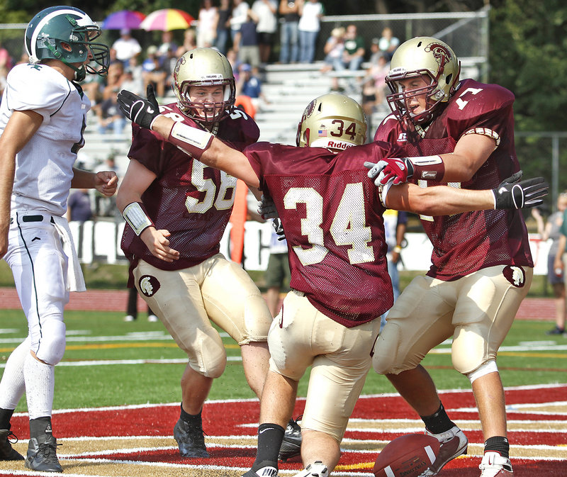Keith Parenteau, 58, and Tyler Danley, 77, celebrate with teammate Nick Kenney after Kenney scored the first touchdown for Thornton Academy on a 9-yard run late in the second quarter Saturday. Thornton went on to open the season with a 20-6 victory at home against Bonny Eagle.