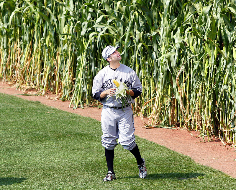 Kyle Fernandes of the Portland Sea Dogs emerges from the corn in centerfield, shucking an ear, before the start of a game against the New Hampshire Fisher Cats at Hadlock Field on Sunday. The cornstalks are from Pumpkin Valley Farm in Dayton, where last year's corn maze included a Sea Dogs logo and an outline of Slugger.