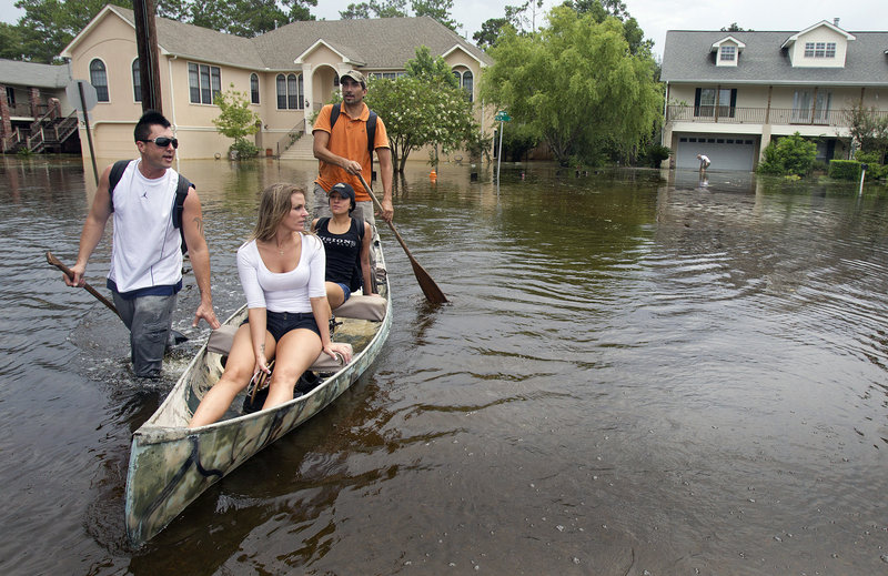 From left, Kevin Porche, Marci Ory, Aline Rodriguez and Michael Rodriguez make their way to the Rodriguez home Sunday in Slidell, La., east of New Orleans, after Tropical Storm Lee flooded the neighborhood.