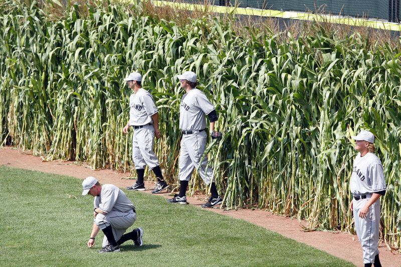 Portland Sea Dogs manager Kevin Boles kneels down to feel the grass of Hadlock Field as his players emerge from the corn in centerfield.