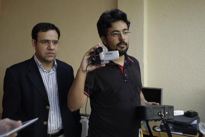 "Umar Saif, left, works with his colleague Yaser Awan in Lahore, Pakistan. Only 11 percent of all Pakistanis use the Internet, but many more use cell phones. ""The thing to do is bring whatever you have on the Internet on the phone lines, because that is what gets used the most,"" Saif said."