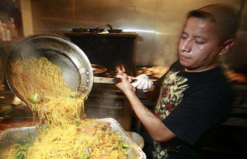 Israel Hernandez prepares food at the Bamboo Grove Hawaiian Grille in Portland, Ore. Service firms grew at slightly faster pace in August compared with July, but the sector remains weak.