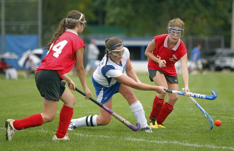 Hannah King of Kennebunk fires the ball away from Alicia Noonhester, left, and Stacey Livingston of Sanford during a Western Class A field hockey game Tuesday. Sanford, seeking a return to the playoffs this season, improved to 2-0 with a 2-0 victory on the road.