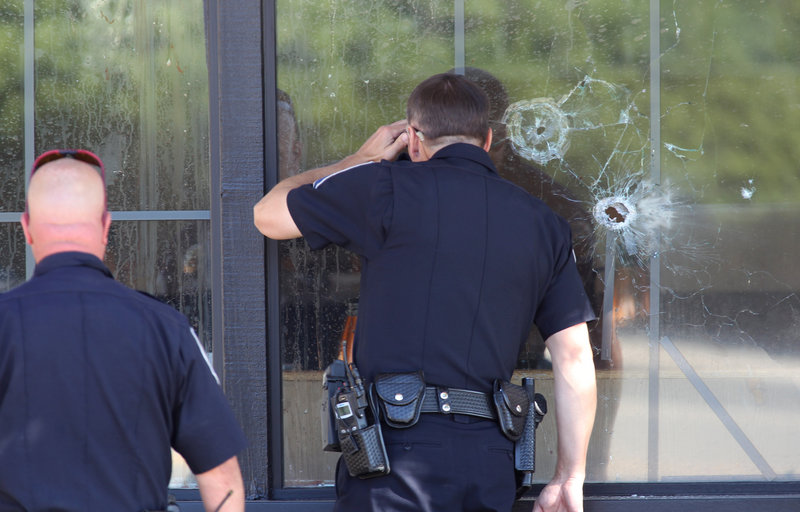 Officers look through a bullet-damaged window of an IHOP restaurant in Carson City, Nev., on Tuesday, after a gunman opened fire at the restaurant, killing two National Guard members and another person. The gunman later killed himself.
