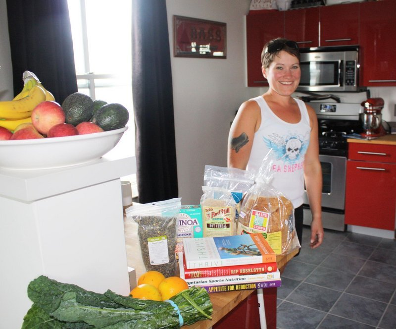 Angela May Bell stands in her Portland kitchen surrounded by some of the vegan foods she s been eating as she prepares to run the Maine Marathon.