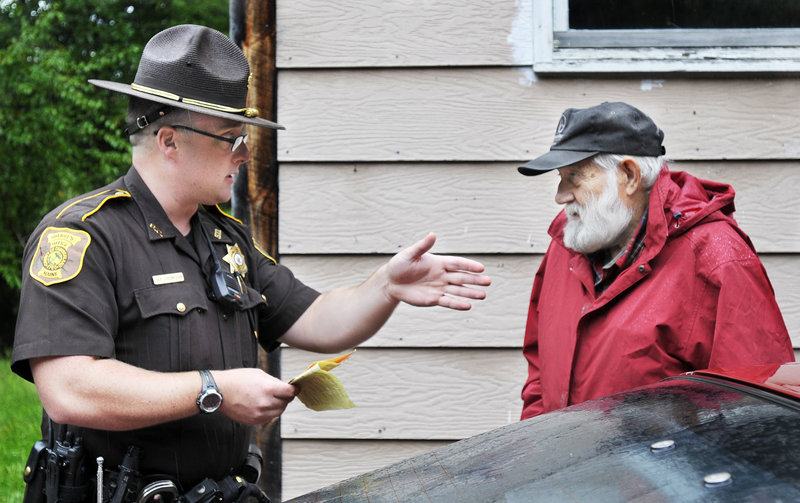 """Deputy Matthew Thompson gives a temporary inspection permit to a Gray resident. Thompson will """"use enforcement when necessary and do some problem-solving with people who have quality-of-life issues,"""" said Sheriff Kevin Joyce."""