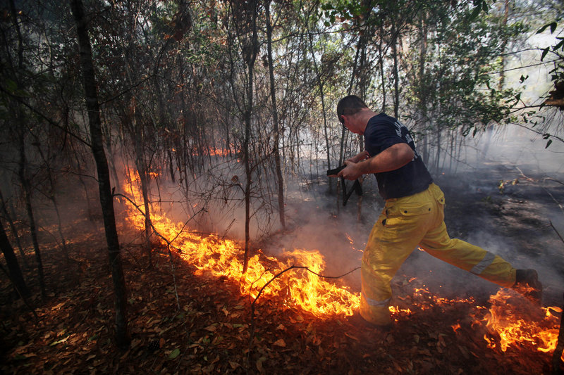 A firefighter jumps across the fire south of Todd Mission, Texas, in Waller County on Wednesday. Firefighters made progress against one of the most destructive wildfires in Texas history. The fire has claimed more than 33,000 acres, 800 homes and two lives.
