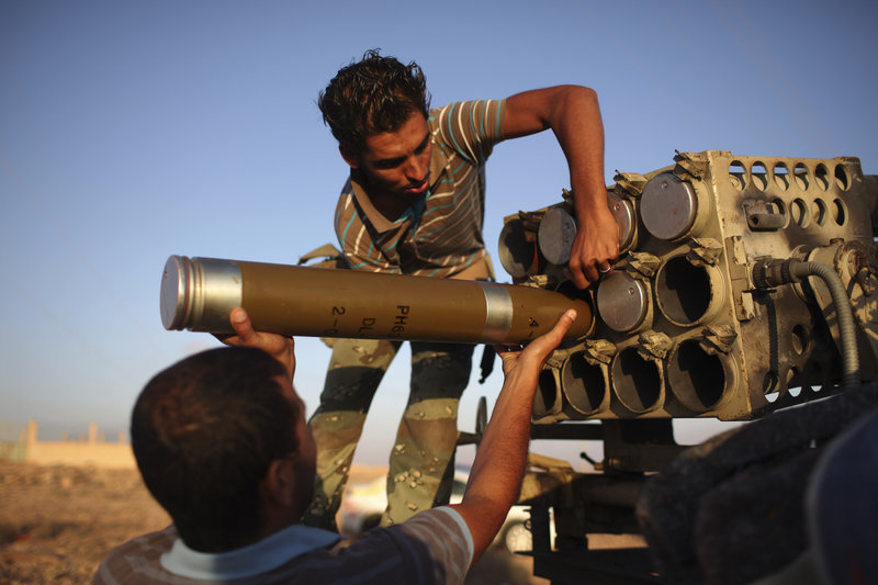 Libyan fighters prepare a projectile at a checkpoint between Tarhouna and Bani Walid on Thursday. Thousands of fighters have converged outside Bani Walid and have threatened to attack if residents don't surrender by Saturday.