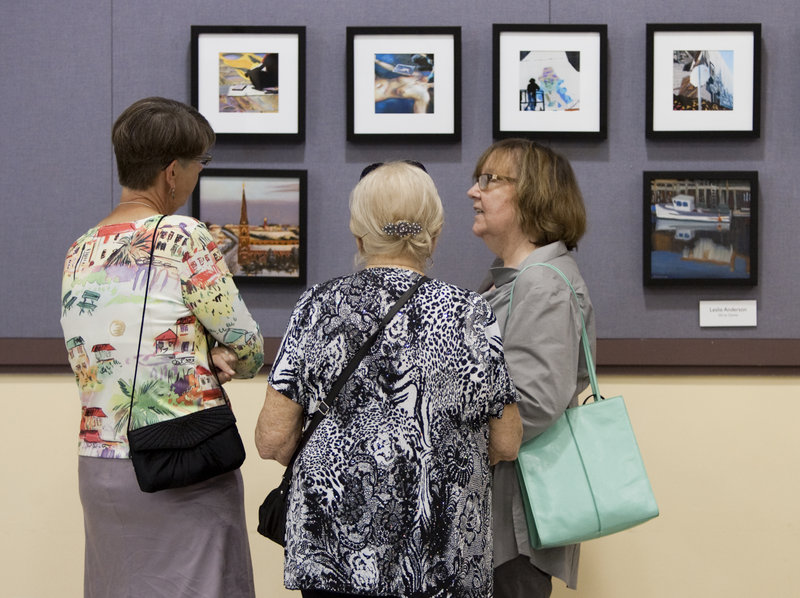Leslie Anderson, Priscilla Krasnow and Julie Maranan, all of Portland, have a discussion at the Black Frame Art Sale in the Merrill Auditorium rehearsal hall Friday. Last year, the annual event raised about $6,000, organizers said.