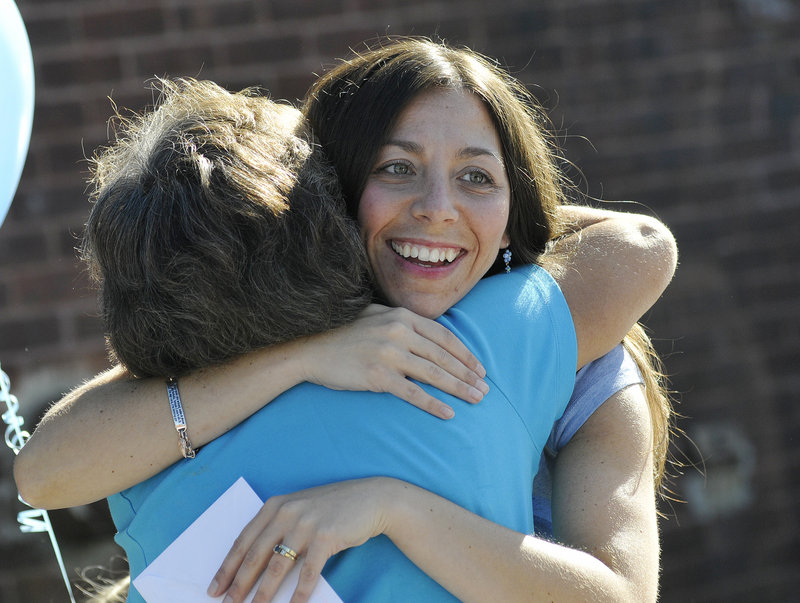Christina Mahaney, mother of Liam Mahaney, gets a hug prior to the benefit walk Saturday in Biddeford.