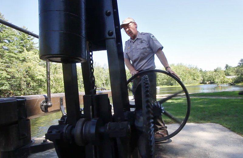 Sam Chute of the Maine Department of Conservation operates the hand-turned mechanism that opens and closes the Songo Lock. Passing through the historic lock has been one attraction of riding on the Songo River Queen II.