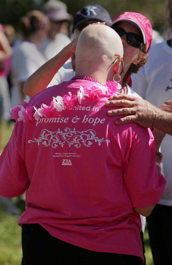 Debbie Boothby of Raymond, in the early stages of cancer treatment, has her shaved head touched by a fellow participant Sunday.