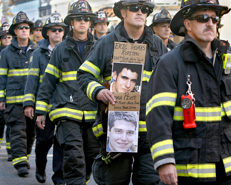 Beau Gleason of the Portland Central Fire Station carries pictures of friends from college, who died on the 105th floor in the north tower of the World Trade Center, during a procession along Congress Street in Portland as part of Sunday's Sept. 11 observance.