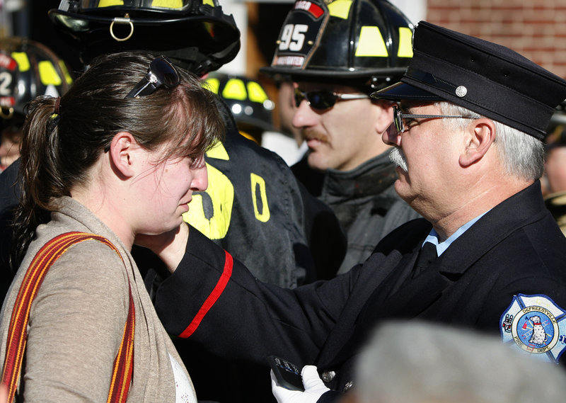 Bob Ewing, a volunteer firefighter with the DeFreestville, N.Y., Fire Department who was part of a rescue and recovery group that went to New York City after the attacks on Sept. 11, 2001, wipes tears from the face of his daughter, Hannah Ewing of Portland, before participating in Portland's 10th anniversary observance Sunday.