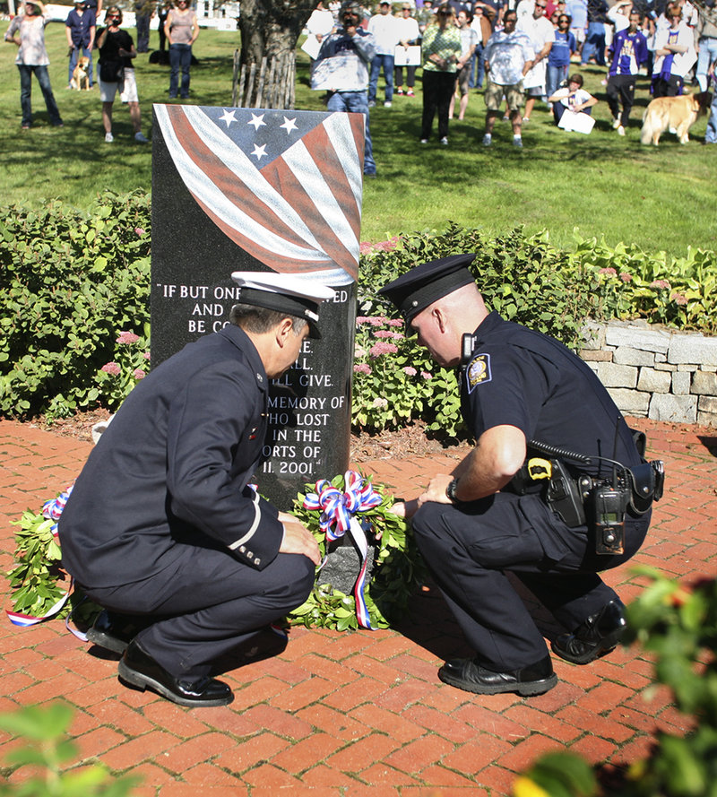Lt. John Brooks of the Munjoy Hill Fire Station, left, and Kevin Haley of the Portland Police Department lay a wreath at the 9/11 Memorial at Fort Allen Park on the Eastern Promenade in Portland on Sunday.