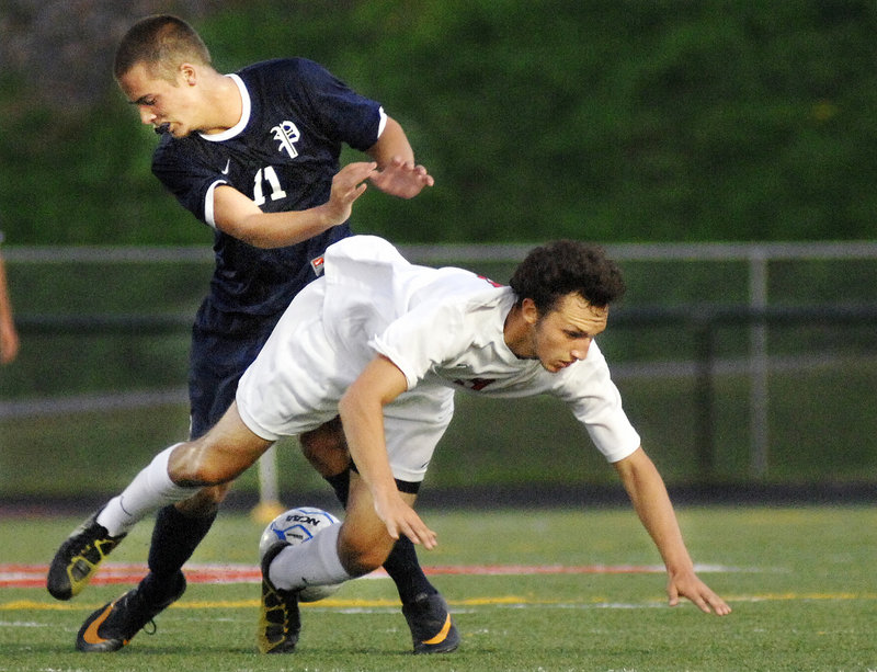 Andrew Jones of Scarborough takes a tumble after running into Paley Burlin of Portland during an SMAA boys' soccer game Tuesday night at Scarborough. The teams played to a 0-0 tie.