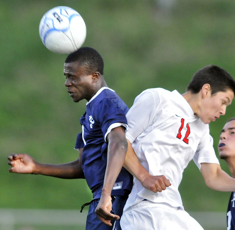 Tony Yekeh of Portland gets a head on the ball while jousting with Scarborough's JD Herrman during a game Tuesday night at Scarborough. The teams tied, 0-0.