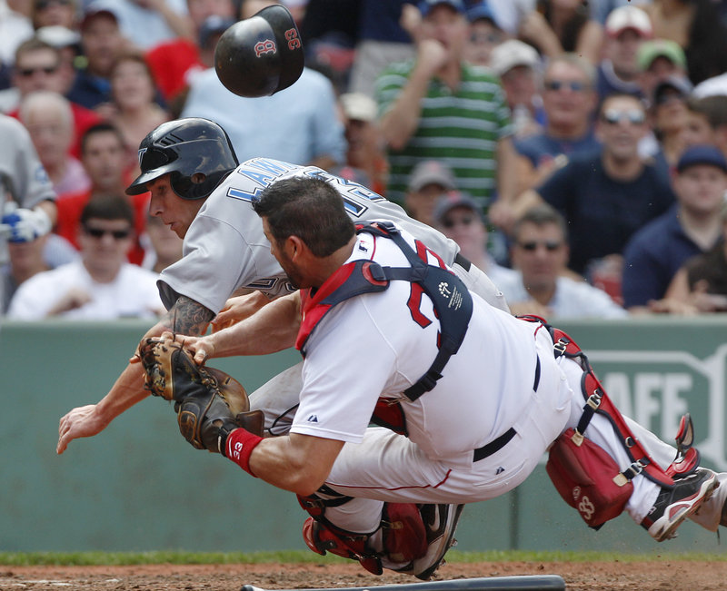 Jason Varitek holds the ball for the out Wednesday after a collision with Brett Lawrie of the Blue Jays, trying to score on a grounder. Toronto rallied to win, 5-4.
