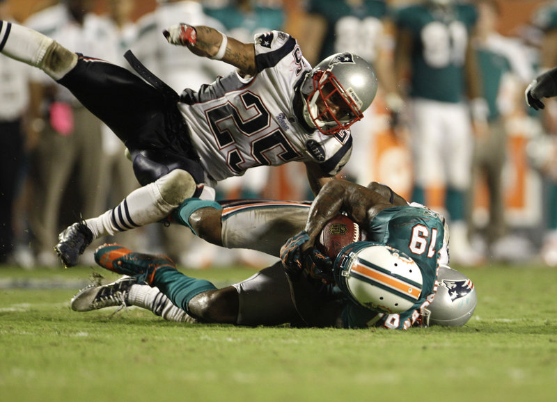 Patrick Chung, top, and Devin McCourty, back, take down Miami's Brandon Marshall in Monday night's game. McCourty led the Patriots with 11 tackles, but the Dolphins threw for 416 yards against New England's secondary.