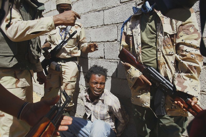 Revolutionary fighters arrest a man from Nigeria, who they allege is a Gadhafi loyalist, as they take control of villages in the desert Saturday about 450 miles south of the Libyan capital of Tripoli. The former leader remains in hiding.