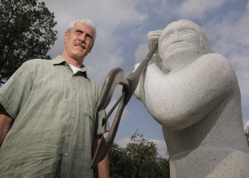 John Banks, natural resources director for the Penobscot Indian Nation, stands next to a sculpture of a native fisherman on Indian Island.