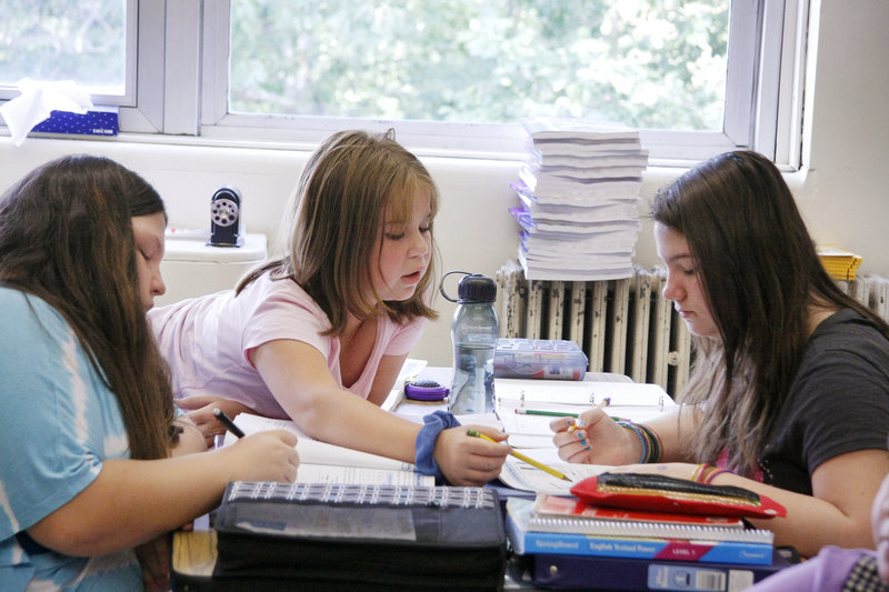 Sixth-grader Stephanie Lane, center, helps classmate Sierra Hussey, right, while working on a math assignment along with classmate Madalynn Gagne, left, in Barbara Noone's girls-only class at Willard School in Sanford.