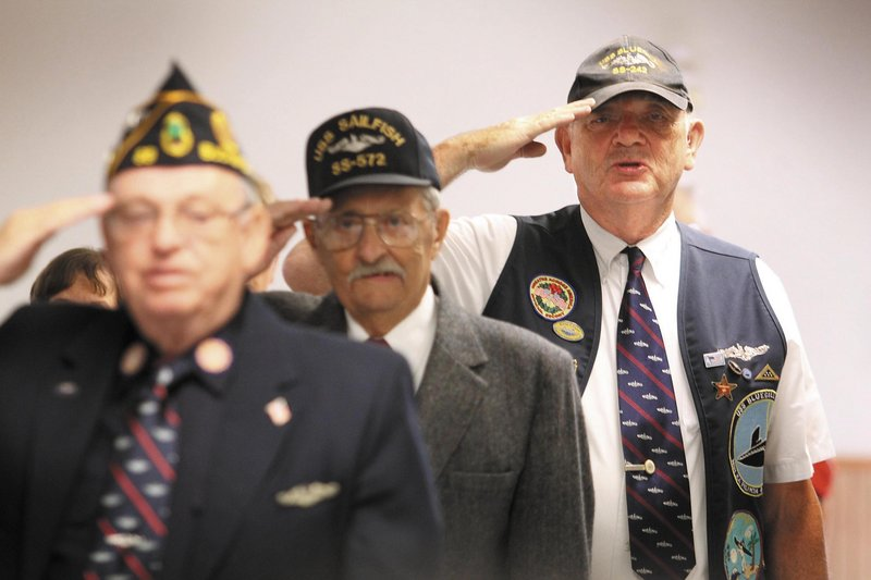 John McCutcheon, right, of Fairfield joins Norman McLeod, center, of Portland and Lyle Grindle, left, of Dedham in reciting the Pledge of Allegiance during an induction ceremony into the Holland Club for having attained 50 years since first qualifying to serve on submarines, at the American Legion Post 205 in Augusta on Sunday.