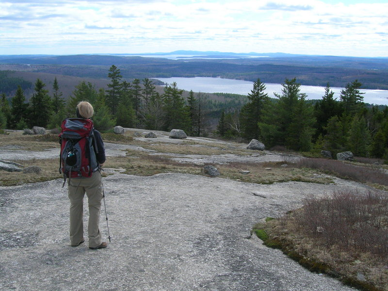 A hiker atop Flag Hill takes in the view across Branch Lake below, one of several impressive vistas in Great Pond Mountain Wildlands in East Orland, between Bucksport and Ellsworth.