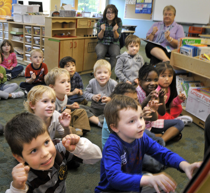 Kindergarten students at Ocean Avenue Elementary School listen Thursday as teacher Juanita DeWitt reads a story. The school's four kindergarten classes average 22 students, more than the 16 to 20 recommended in district guidelines.