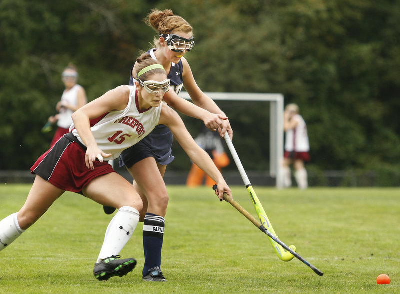 Katie Turner, front, of Freeport pushes the ball ahead of Traip Academy's Anna Powers during their Western Maine Conference field hockey game Friday at Freeport. Turner scored the winning goal as the Falcons improved to 6-2 with a 3-2 victory.