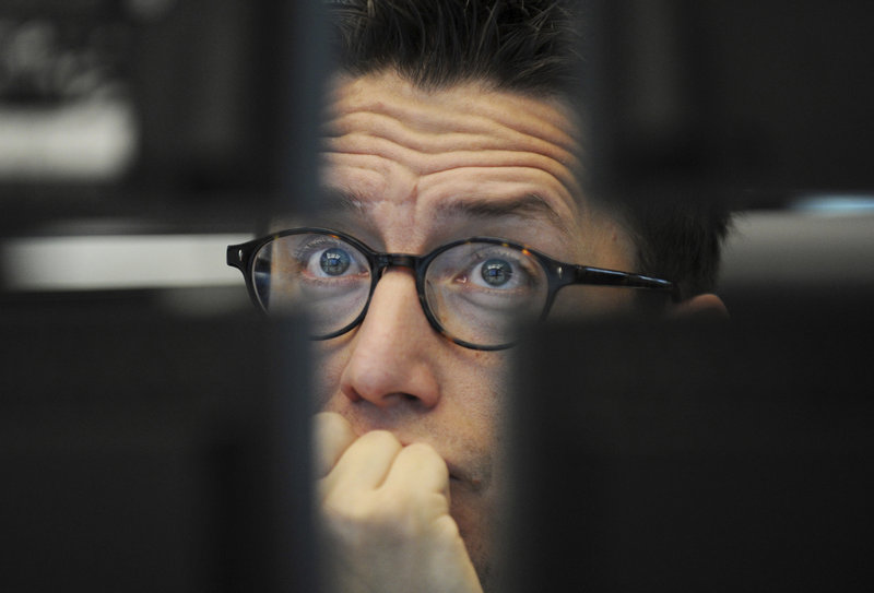 A trader watches his screens at the German stock exchange in Frankfurt on Friday. An action plan unveiled by the G-20 countries Thursday to help Greece avoid a destabilizing default did not immediately soothe fearful investors.