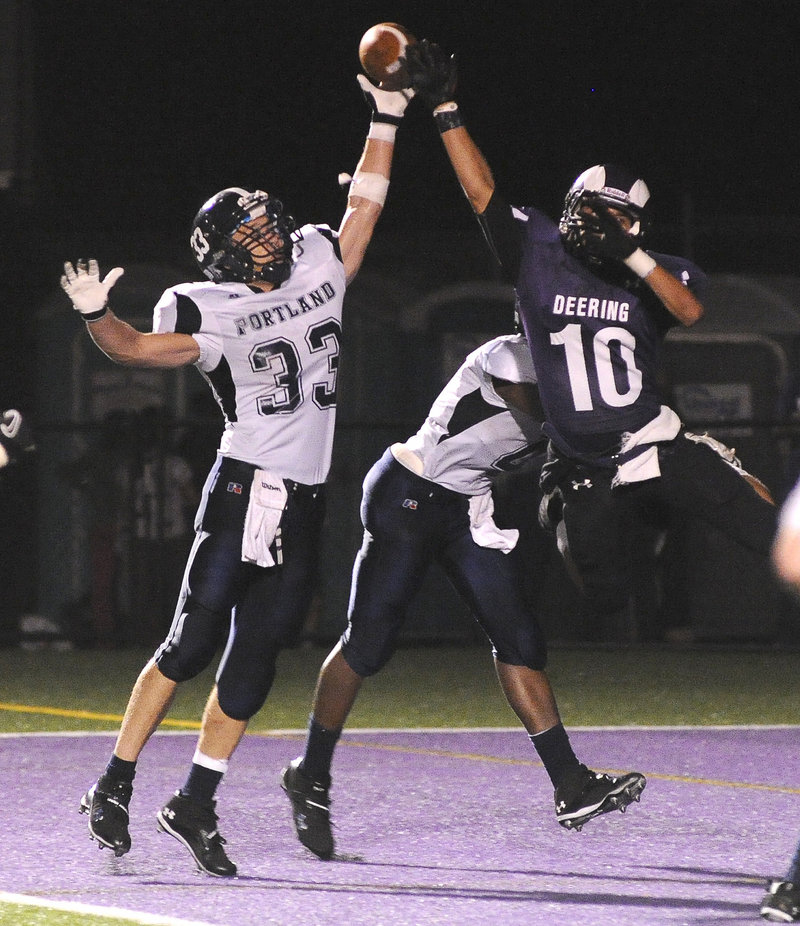 Mike Herrick, left, of Portland breaks up a pass intended for Renaldo Lowry of Deering during their football game Friday night. Deering remained unbeaten with a 28-7 victory.