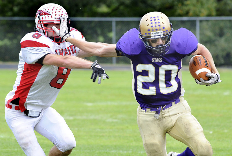 Spencer Cooke, who ran for two touchdowns and caught a pass for a third for Cheverus, stiff-arms Dan Webb of Sanford on the way to a gain Saturday at Boulos Stadium. Cheverus came away with a 41-8 victory.