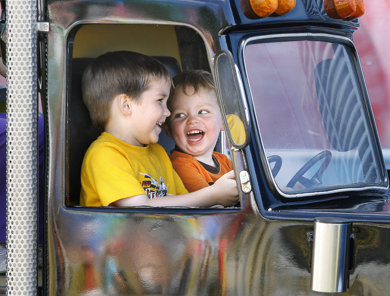 Logan Plourde, 5, of Scarborough, left, and Jack Mesires, 2, of Gorham find reason to laugh on one of the kiddie rides at the Cumberland County Fair on Sunday.