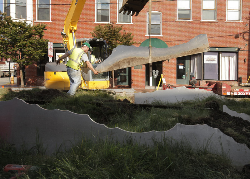 "At top, Evan Brainerd of Coastal Lawn Care guides a section of ""Tracing the Fore"" to a truck on Fore Street in Portland on Monday. PWM Land bought the $135,000 piece for $100 and is paying about $9,000 to remove it from Boothby Square. It will be installed in a North Deering sculpture garden."