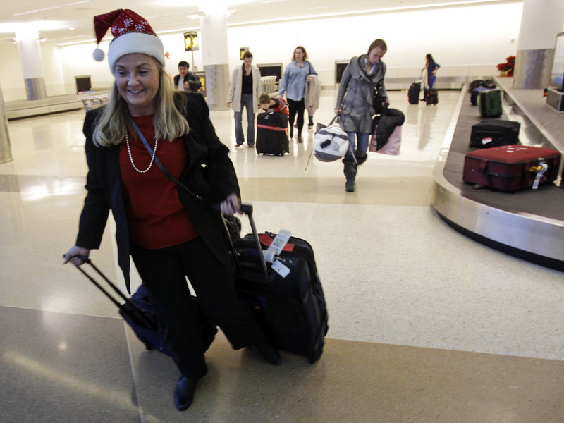 Christmas travelers collect their luggage at San Jose International Airport. Flying on a holiday can cut the cost of airfare.
