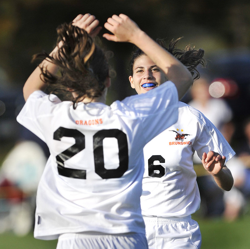 Dakota Foster, 20, of Brunswick celebrates with Cassandra Murano after scoring one of her three goals Tuesday in a 5-0 victory against Messalonskee.