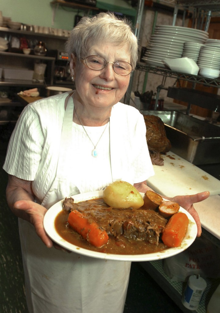 Ines De Costa shows off her New England pot roast with added Portuguese chiroco sausage in Fall River, Mass., in April 2008. Celebrity chef Emeril Lagasse, as a boy, liked to watch Mrs. De Costa in her restaurant kitchen and he maintained a loving, lifelong relationship with her.