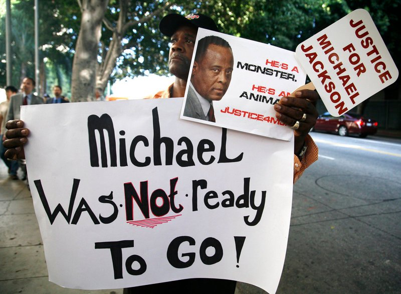Bristre Clayton, a Michael Jackson fan from Las Vegas, shows his opinion outside court in Los Angeles on Tuesday during the opening day of Dr. Conrad Murray's trial. Jackson's personal physician is charged with involuntary manslaughter in the singer's death from drugs in 2009.