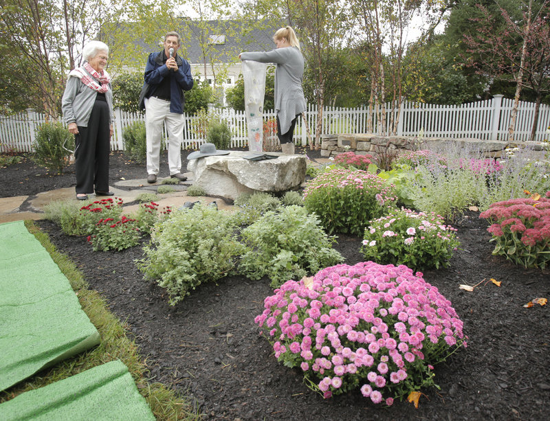 """Barbara Bush looks at a bench holding bronze versions of her floppy hat, her favorite book, """"Pride and Prejudice,"""" and her favorite sneakers, Keds, Thursday during the dedication of a town garden named after her in Kennebunkport. At center is family friend Ken Raynor, and at right is granddaughter Marshall Bush."""