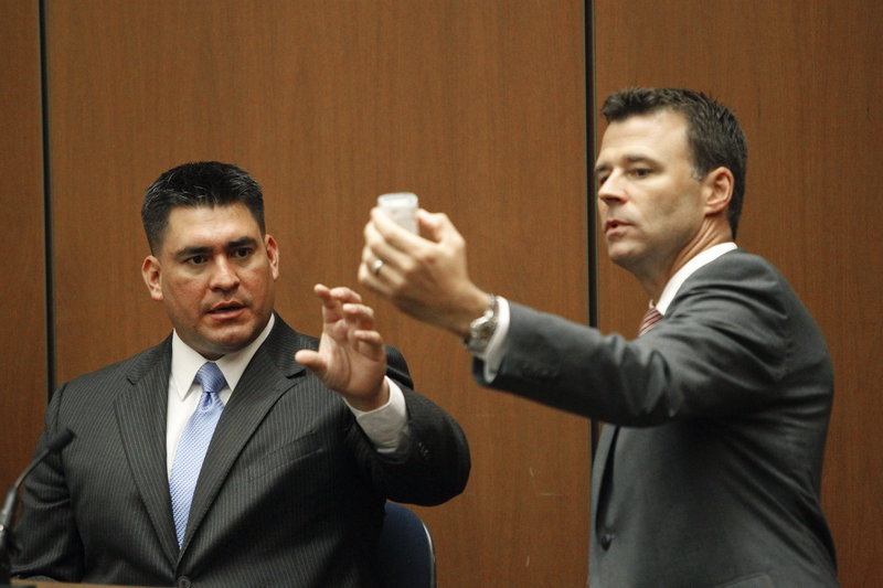 Deputy District Attorney David Walgren holds a bottle of propofol while questioning Alberto Alvarez, one of Michael Jackson's security guards, during Conrad Murray's involuntary manslaughter trial Thursday.