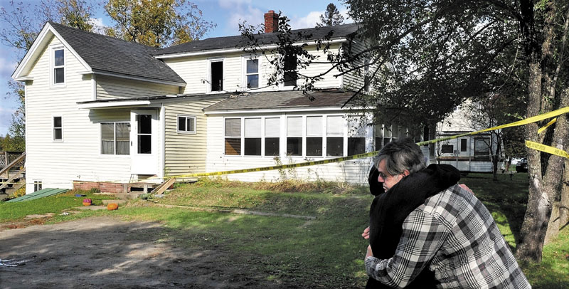 COMFORT: Homeowner Mellaney Drew is consoled by neighbor Mike Parlin outside Drew's home in Hartland on Monday as an investigator with the state Fire Marshal's Office and Hartland Fire Chief Don Neal try to determine the cause of the fire that seriously damaged the home Saturday night.