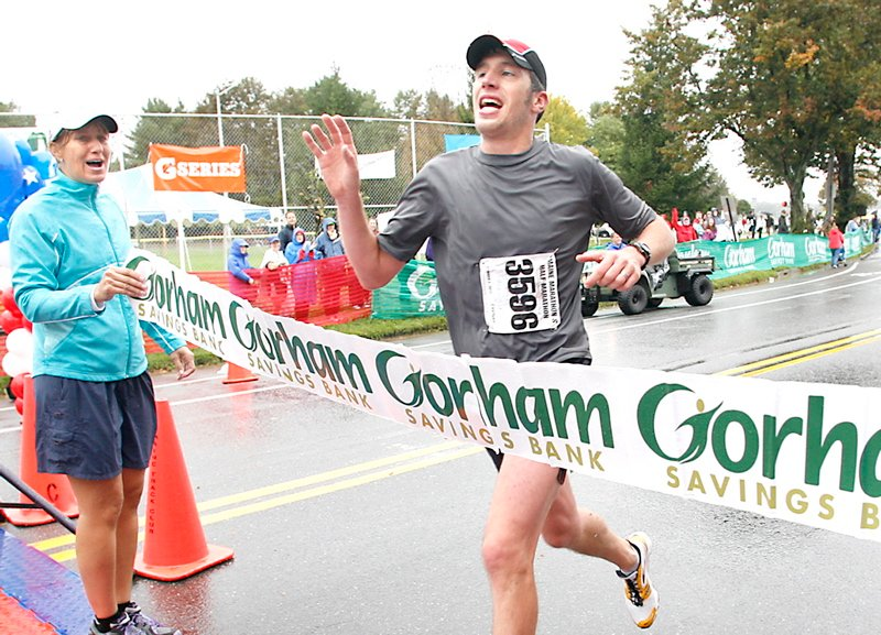 Maine Marathon winner Evan Graves waves to supporters as he crosses the finish line during the 20th running of the Maine Marathon today in Portland.