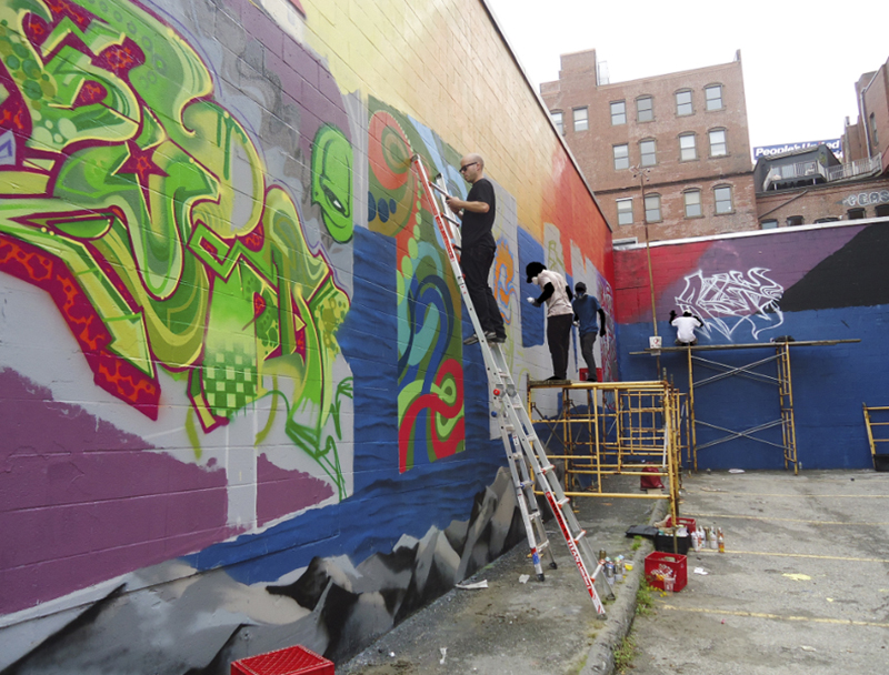 Matt W. Moore, front, and other artists work on the mural at the Asylum nightclub. They also painted three other walls of the building, one of which includes a whimsical puffin.