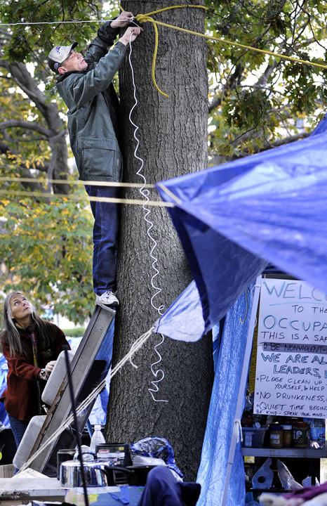 Alan Porter, 45, of Portland shimmied up a tree in Lincoln Park to secure a rope as part of a support system for a tarp to protect Occupy Maine's belongings against impending rain.