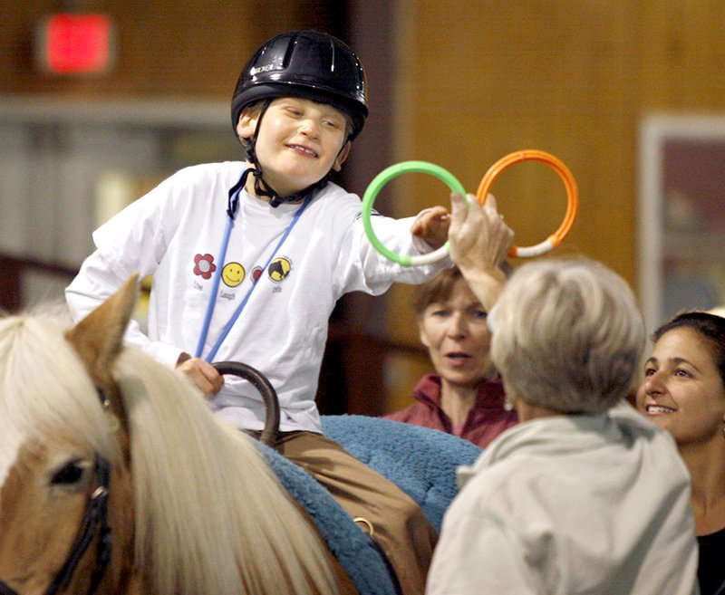 Sarah Bronson, executive director of the Riding to the Top Therapeutic Riding Center in Windham, holds up rings for Scotty Wentzell, 10, to grab as Diane Powers of the riding center, middle, and Scotty's mother, Lisa Wentzell, encourage him.