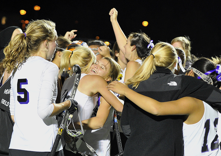 Marshwood High School's Hailey Bruno-Moulton, center, hugs Emily Osborne just after their field hockey team's 4-1 victory over Portland in the Class A Western Maine Regional Final on Tuesday night at Hill Stadium in Saco. York High School won the Class B title over Mountain Valley, and North Yarmouth Academy beat Sacopee Valley in Class C.
