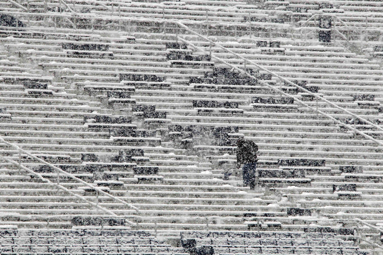 A worker shovels snow from the seats in preparation for an NCAA college football game between Penn State and Illinois at Beaver Stadium in State College, Pa., today.